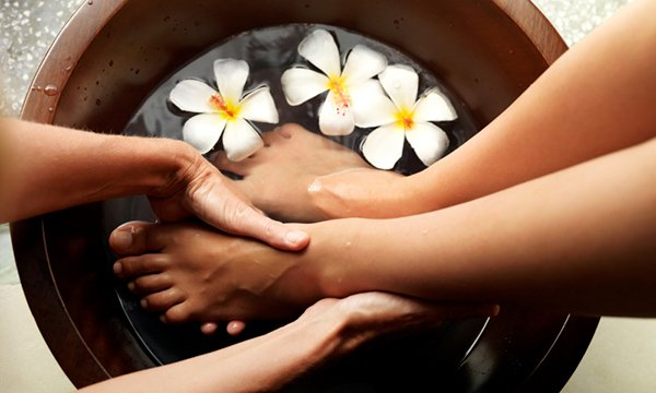 Female feet in foot bath with flowers getting pedicure